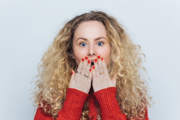 Emotional lovely woman with unexpected look covers mouth with hand