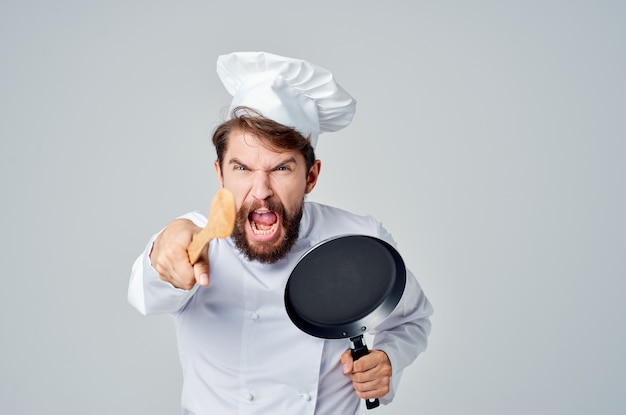 Emotional male chef frying pan in hand cooking cooking food