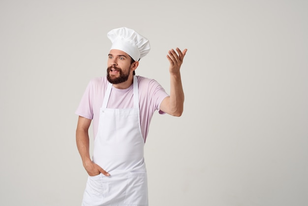 Emotional male chef in white apron gesturing with his hands professional cooking