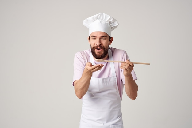 Emotional male chef in a white apron is trying food
