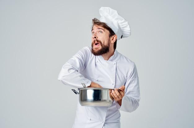 Эмоциональный шеф-повар-мужчина с кастрюлькой в руках, готовящей ресторанное дело. фото высокого качества