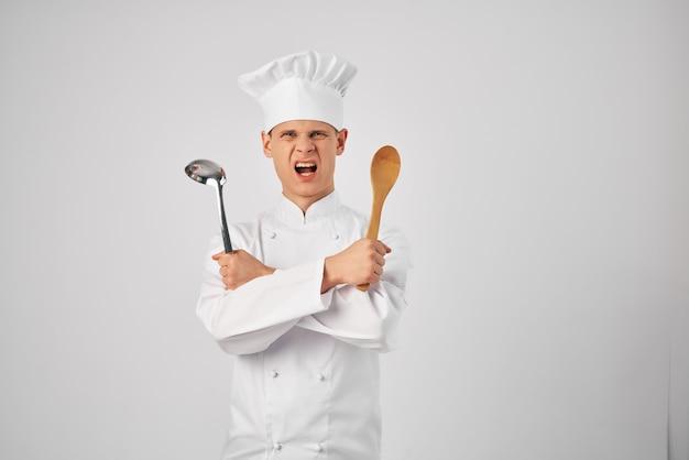 レストランの料理で働く台所用品を持つ感情的な男性シェフ。高品質の写真