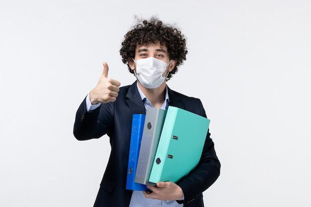 スーツを着て、白い表面で大丈夫なジェスチャーをするドキュメントを保持している彼のマスクを身に着けている感情的な男性起業家