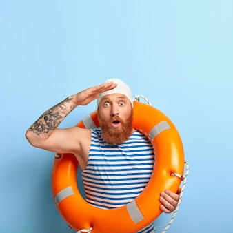 Il bagnino maschio emotivo fissa in lontananza, nota la persona che affonda in mare, aiuta le persone a sopravvivere
