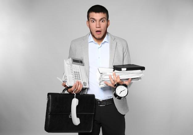 Эмоциональный менеджер-мужчина с офисными вещами на сером фоне