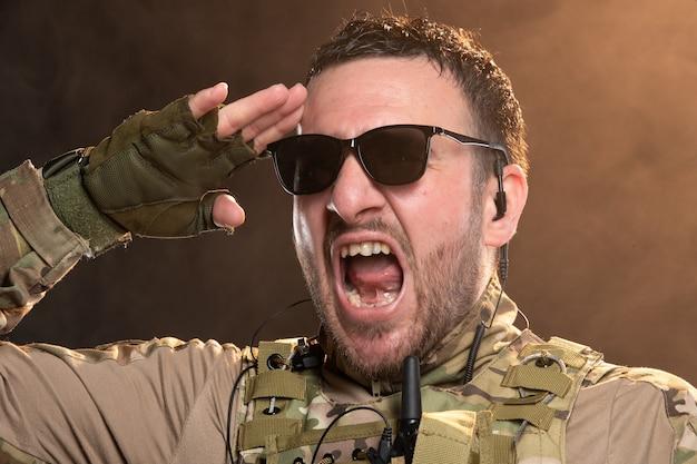 어두운 연기가 자욱한 벽에 경례하는 위장에 감정적 인 남성 군인