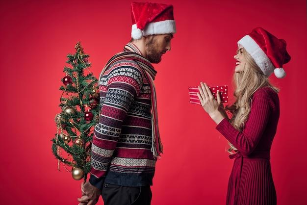 感情的な男性と女性の贈り物クリスマス新年赤い背景。高品質の写真