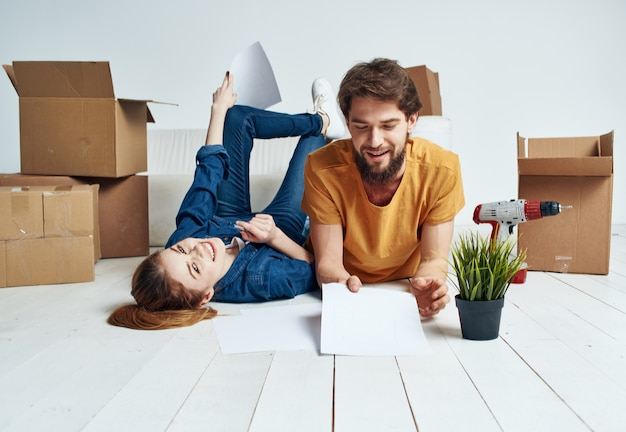 移動するリフォーム作業を楽しんでいる床に段ボール箱を持つ感情的な男性と女性