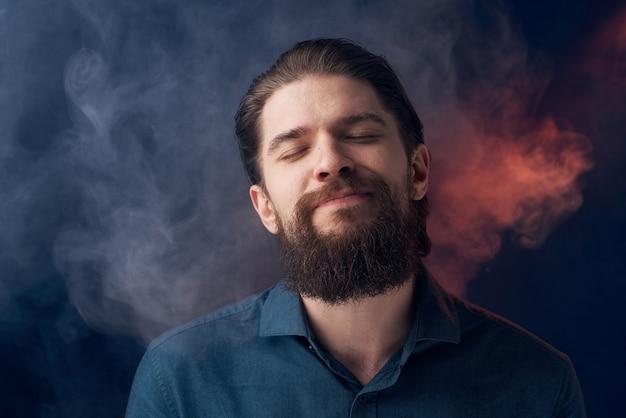 感情的な男の黒いシャツの魅力的な外観のクローズアップの煙が背景にあります。