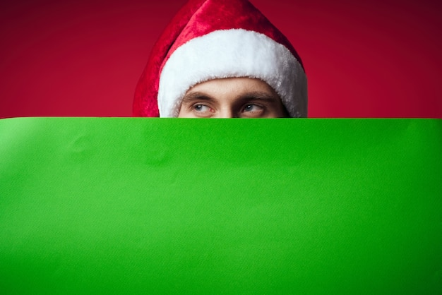 Emotional man in a christmas hat with green mockup studio posing