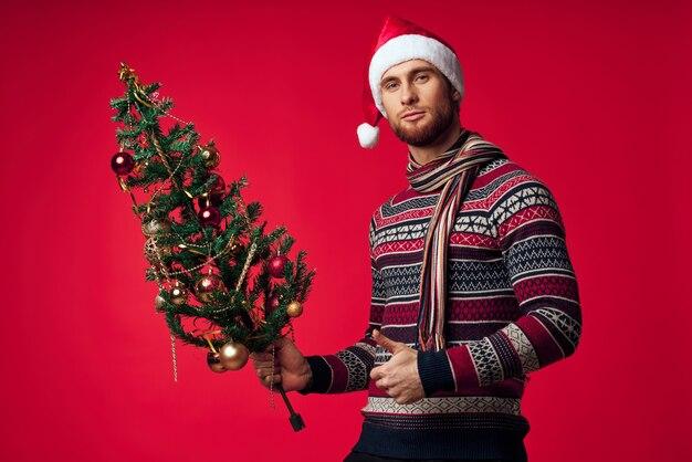 感情的な男のクリスマスツリーのおもちゃ新年の赤い背景