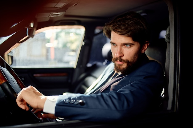 Emotional man driving a car trip luxury lifestyle communication by phone. high quality photo