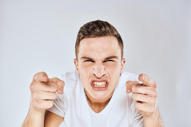 手で身振りで示す感情的な男は、表情を不快にさせた白いtシャツをトリミング