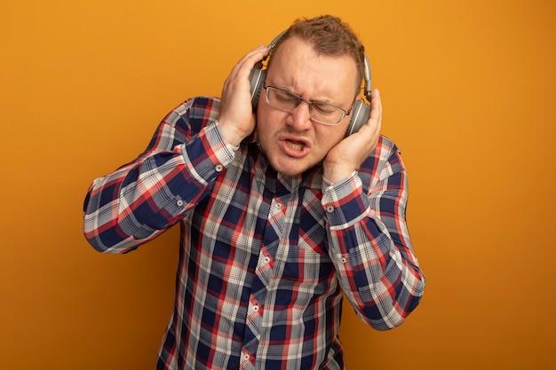 Uomo emotivo in bicchieri e camicia a quadri con le cuffie per godersi la musica in piedi sopra la parete arancione