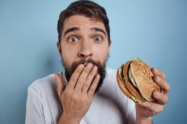 감정적 인 남자 햄버거 패스트 푸드 다이어트 음식 근접 파란색 배경. 고품질 사진