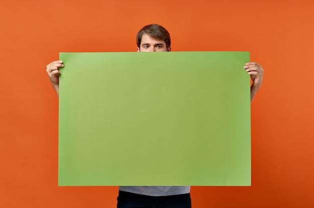 緑のバナーデザインスタジオのライフスタイルを保持している感情的な男