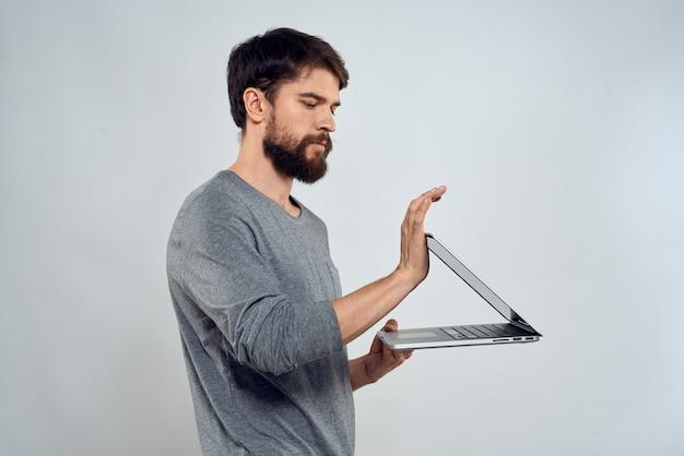 ノートパソコンの成功を保持している感情的な男モダンなスタイルの作業灯。