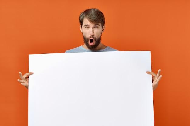 モックアップポスター割引オレンジ色の背景を保持している感情的な男