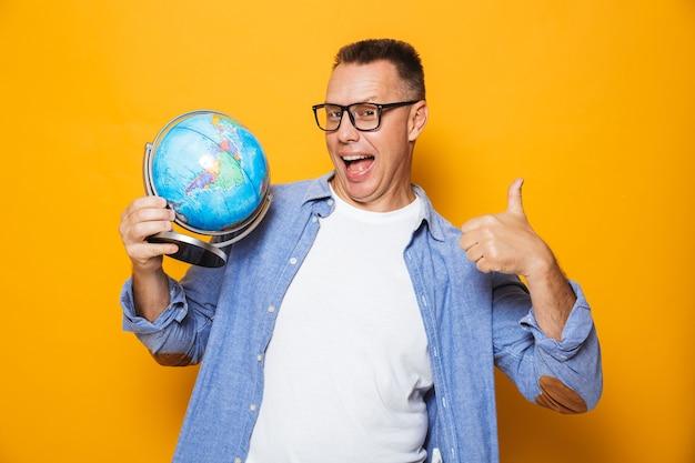 Эмоциональный человек, держащий земной шар, делает большие пальцы руки вверх жест.