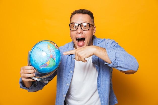 Эмоциональный мужчина держит указывая глобус.