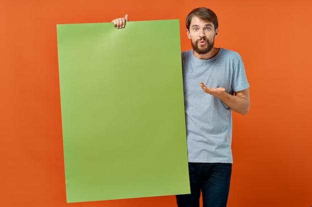 Эмоциональный мужчина держит в руке рекламный плакат мокап