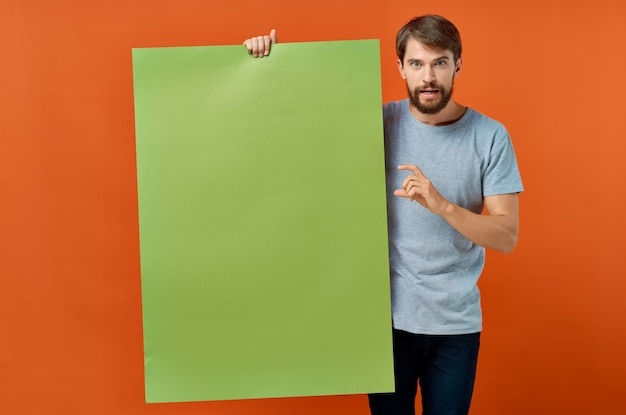 Эмоциональный мужчина держит в руке рекламную коммуникацию плаката мокап.