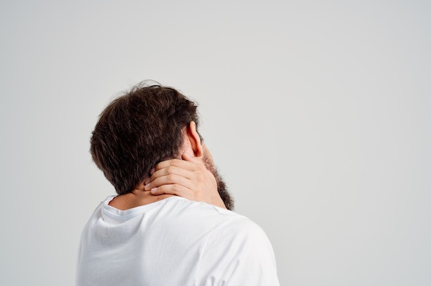 Emotional man holding neck arthritis health problems light background