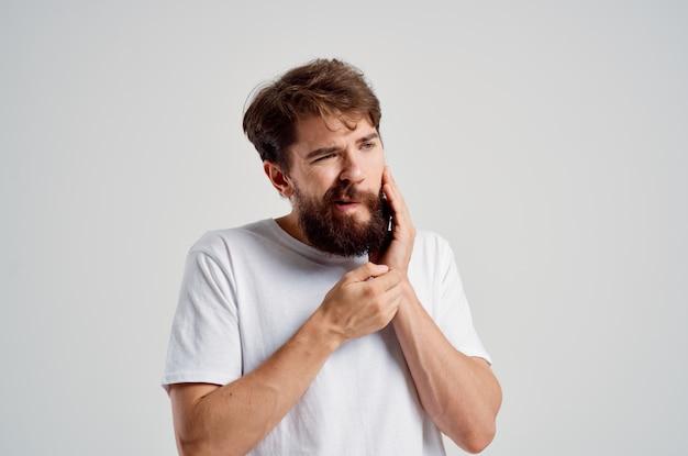 치아 고립 된 배경에서 얼굴 통증을 잡고 감정적인 남자. 고품질 사진