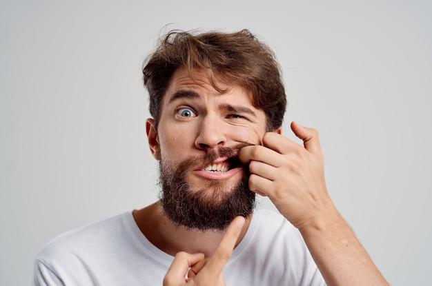 Эмоциональный мужчина держится за боль в зубах на изолированном фоне
