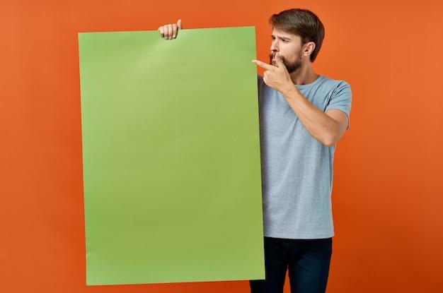 Эмоциональный мужчина держит в руке рекламный плакат.