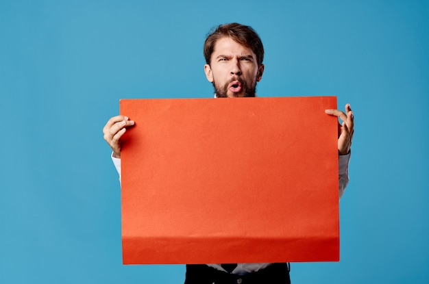 Emotional man holding red banner communication advertising isolated blue wall.