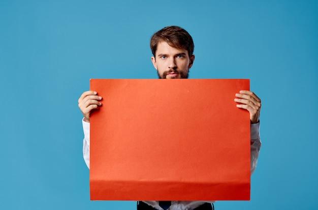 Эмоциональный человек, держащий красное знамя коммуникационной рекламы, изолировал синюю стену.