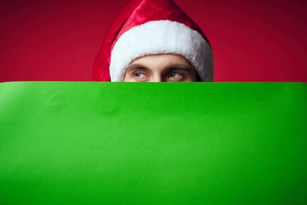 Эмоциональный мужчина в новогодней шапке с зеленым студийным макетом позирует