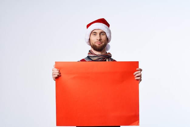 빨간 모형 포스터 밝은 배경을 가진 크리스마스 모자를 쓴 감정적인 남자. 고품질 사진