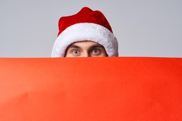 빨간색 목업 포스터 밝은 배경이 있는 크리스마스 모자를 쓴 감정적인 남자