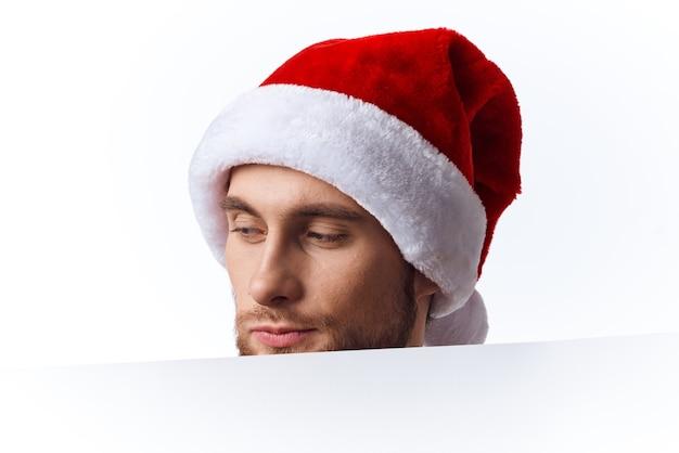白いモックアップポスタークリスマスライトの背景を持つクリスマス帽子の感情的な男。高品質の写真