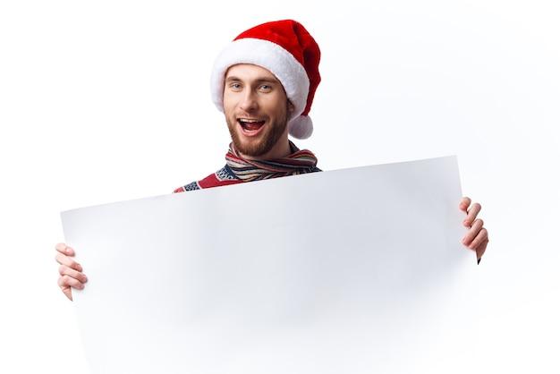 흰색 모형 포스터 크리스마스 밝은 배경이 있는 크리스마스 모자를 쓴 감정적인 남자. 고품질 사진