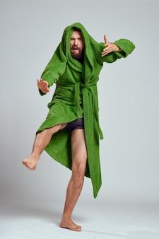 完全な成長の楽しい感情モデルの明るい背景に緑のローブの感情的な男。高品質の写真