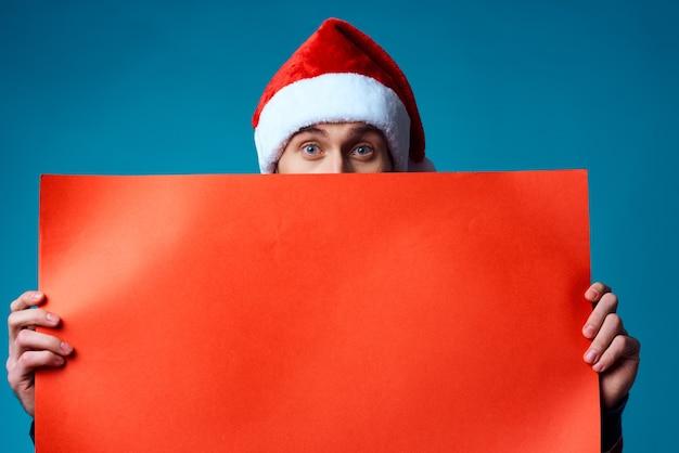 バナーの休日の青い背景を保持しているサンタ帽子の感情的な男。高品質の写真
