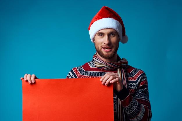 Эмоциональный мужчина в шляпе санта-клауса держит баннер праздник синий фон