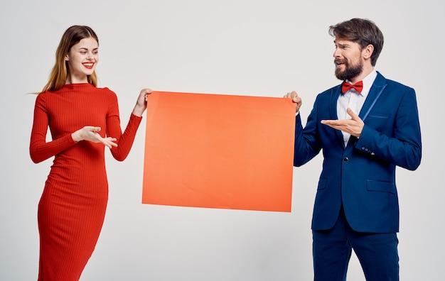 Эмоциональный мужчина в костюме и галстуке-бабочке с макетом в руках и молодая женщина