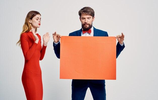 Эмоциональный мужчина в костюме и галстуке-бабочке с макетом в руках и молодая женщина.