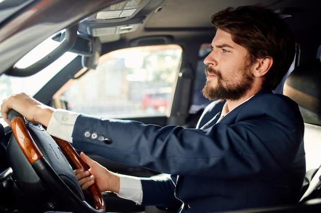 車の中でスーツを着た感情的な男は自信を持って働くための旅行。高品質の写真