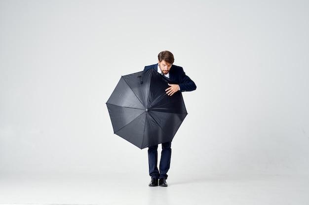 手に傘を持ったスーツを着た感情的な男悪天候