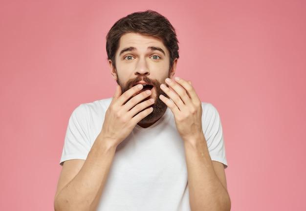 흰색 티셔츠를 입은 감정적인 남자는 표정 분홍색 배경에 짜증을 냈다. 고품질 사진