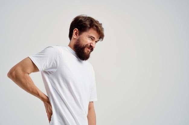 白いtシャツの感情的な男ストレス医学腰痛明るい背景
