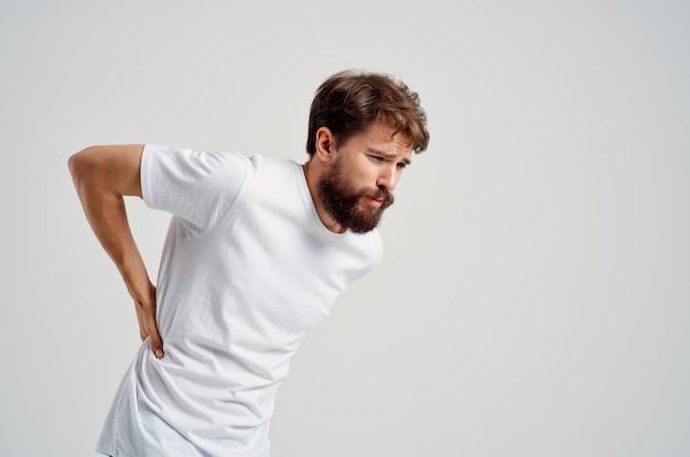 白いtシャツの感情的な男ストレス医学腰痛スタジオ治療