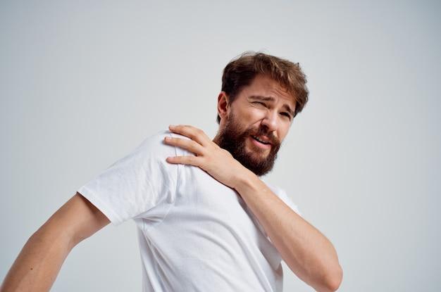 白いtシャツの感情的な男は、首の孤立した背景の薬の痛みを強調します