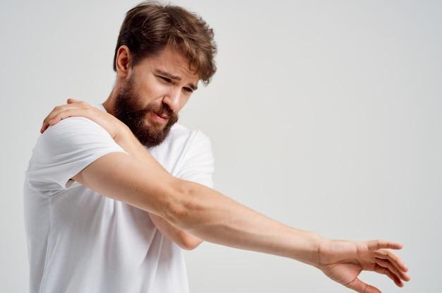 Эмоциональный мужчина в белой футболке снимает стресс, снимает боль в шее.