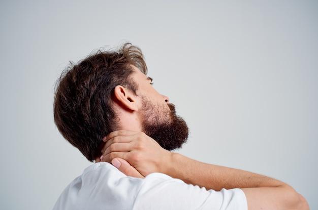 白いtシャツを着た感情的な男は首のスタジオ治療で薬の痛みを強調します